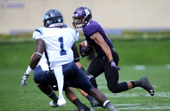 Sep 21, 2013; Evanston, IL, USA; Northwestern Wildcats wide receiver Tony Jones (6) runs past Maine Black Bears defensive back Axel Ofori (1) for a touchdown during the first quarter at Ryan Field.  Mandatory Credit: Jerry Lai-USA TODAY Sports