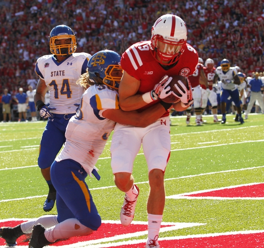 Sep 21, 2013; Lincoln, NE, USA; Nebraska Cornhuskers receiver Sam Burtch (9) catches a touchdown pass against South Dakota State Jackrabbits defender Jake Gentile (38) and Winston Wright (14) in the second quarter at Memorial Stadium. Mandatory Credit: Bruce Thorson-USA TODAY Sports