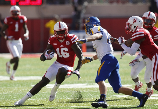 Sep 21, 2013; Lincoln, NE, USA; Nebraska Cornhuskers defender Stanley Jean-Baptiste (16) intercepts the pass and returns it against the South Dakota State Jackrabbits receiver Trevor Tiefenthaler (84) in the second quarter at Memorial Stadium. Mandatory Credit: Bruce Thorson-USA TODAY Sports