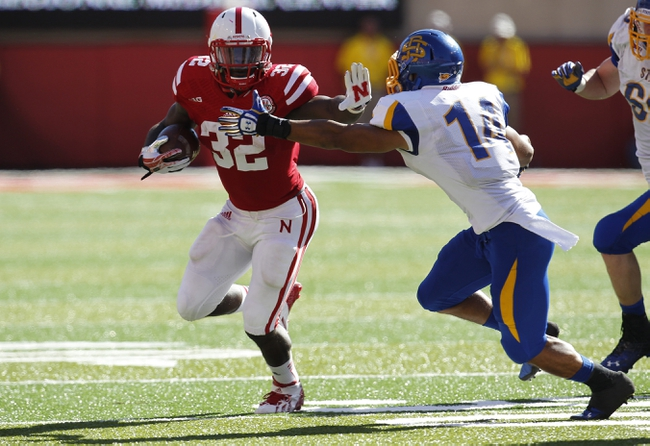 Sep 21, 2013; Lincoln, NE, USA; Nebraska Cornhuskers running back Imani Cross (32) gets away from South Dakota State Jackrabbits defender Winston Wright (14) in the second quarter at Memorial Stadium. Mandatory Credit: Bruce Thorson-USA TODAY Sports