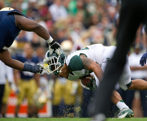 Sep 21, 2013; South Bend, IN, USA; Notre Dame Fighting Irish nose tackle Louis Nix (1) pulls the helmet off Michigan State Spartans running back Nick Hill (20) in the second quarter at Notre Dame Stadium. Nix was called for a face mask penalty. Mandatory Credit: Matt Cashore-USA TODAY Sports