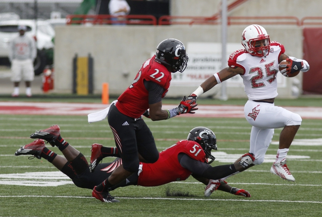 Sep 21, 2013; Oxford, OH, USA; Miami (Oh) Redhawks wide receiver Dawan Scott (25) runs against Cincinnati Bearcats safety Zach Edwards (22) and linebacker Greg Blair (51) during the second quarter at Fred Yager Stadium. Mandatory Credit: David Kohl-USA TODAY Sports