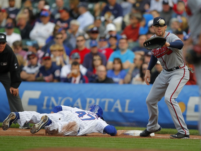 Sep 21, 2013; Chicago, IL, USA; Chicago Cubs left fielder Brian Bogusevic (47) dives into first base with Atlanta Braves first baseman Freddie Freeman (5) taking the throw in the seventh inning at Wrigley Field. Mandatory Credit: Dennis Wierzbicki-USA TODAY Sports
