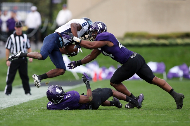 Sep 21, 2013; Evanston, IL, USA; Maine Black Bears wide receiver Derrick Johnson (8) is tackled by Northwestern Wildcats linebacker Chi Chi Ariguzo (44) and cornerback Dwight White (2) during the fourth quarter at Ryan Field.  Mandatory Credit: Jerry Lai-USA TODAY Sports