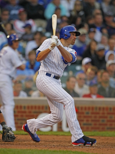 Sep 21, 2013; Chicago, IL, USA; Chicago Cubs right fielder Nate Schierholtz (19) hits an RBI sacrifice fly ball in the eighth inning against the Atlanta Braves at Wrigley Field. Chicago won 3-1. Mandatory Credit: Dennis Wierzbicki-USA TODAY Sports