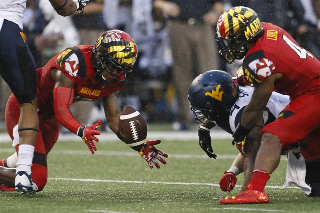 Sep 21, 2013; Baltimore, MD, USA; Maryland Terrapins players recover a fumble by West Virginia Mountaineers running back Wendell Smallwood (4) at M&T Bank Stadium. Mandatory Credit: Mitch Stringer-USA TODAY Sports
