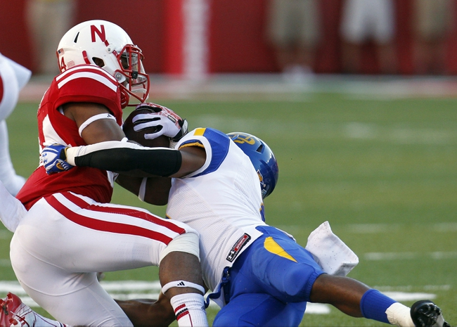 Sep 21, 2013; Lincoln, NE, USA; South Dakota State Jackrabbits defender Melvin Reeves (8) tackles Nebraska Cornhuskers running back Terrell Newby (34) in the fourth quarter at Memorial Stadium. Nebraska won 59-20. Mandatory Credit: Bruce Thorson-USA TODAY Sports