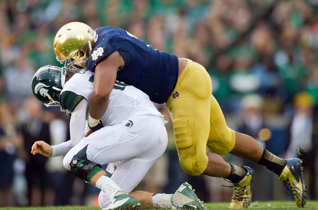 Sep 21, 2013; South Bend, IN, USA; Notre Dame Fighting Irish defensive end Stephon Tuitt (7) sacks Michigan State Spartans quarterback Connor Cook (18) in the fourth quarter at Notre Dame Stadium. Notre Dame won 17-13. Mandatory Credit: Matt Cashore-USA TODAY Sports