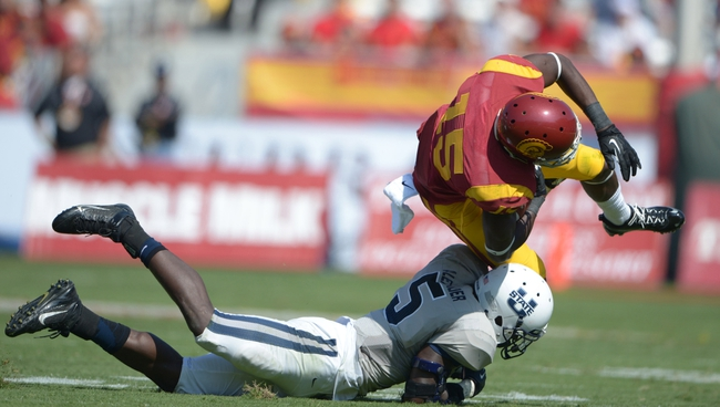 Sep 21, 2013; Los Angeles, CA, USA; Southern California Trojans receiver Nelson Agholor (15) is tackled by Utah State Aggies safety Maurice Alexander (5) at the Los Angeles Memorial Coliseum. USC defeated Utah State 17-14. Mandatory Credit: Kirby Lee-USA TODAY Sports
