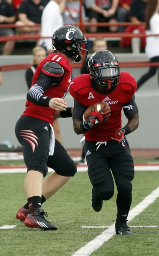 Sep 21, 2013; Oxford, OH, USA; Cincinnati Bearcats quarterback Brendon Kay (11) hands off to running back Ralph Abernathy (1) during a game against the Miami (Oh) Redhawksat Fred Yager Stadium. Cincinnati won 14-0. Mandatory Credit: David Kohl-USA TODAY Sports