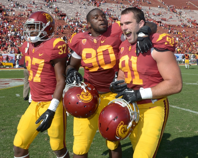 Sep 21, 2013; Los Angeles, CA, USA; Southern California Trojans tailback Javorious Allen (37), defensive end George Uko (90) and linebacker Morgan Breslin (91) celebrate at the end of the game against the Utah State Aggies at the Los Angeles Memorial Coliseum. USC defeated Utah State 17-14. Mandatory Credit: Kirby Lee-USA TODAY Sports