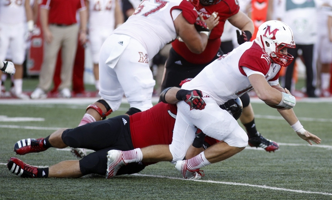 Sep 21, 2013; Oxford, OH, USA; Miami (Oh) Redhawks quarterback Austin Boucher (16) is sacked during a game against the Cincinnati Bearcats at Fred Yager Stadium. Cincinnati won 14-0. Mandatory Credit: David Kohl-USA TODAY Sports