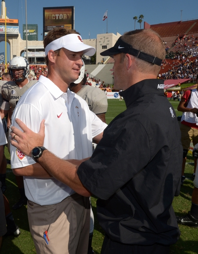 Sep 21, 2013; Los Angeles, CA, USA; Southern California Trojans coach Lane Kiffin (left) shakes hands with Utah State Aggies coach Matt Wells after that the game at the Los Angeles Memorial Coliseum. USC defeated Utah State 17-14. Mandatory Credit: Kirby Lee-USA TODAY Sports