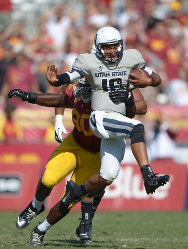 Sep 21, 2013; Los Angeles, CA, USA; Southern California Trojans defensive end George Uko (90) tackles Utah State Aggies quarterback Chuckie Keeton (16) in the fourth quarter at the Los Angeles Memorial Coliseum. USC defeated Utah State 17-14. Mandatory Credit: Kirby Lee-USA TODAY Sports