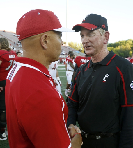 Sep 21, 2013; Oxford, OH, USA; Cincinnati Bearcats head coach Tommy Tuberville (right) shakes hands with Miami (Oh) Redhawks head coach Don Treadwell (left) at the end of their game at Fred Yager Stadium. Cincinnati won 14-0. Mandatory Credit: David Kohl-USA TODAY Sports