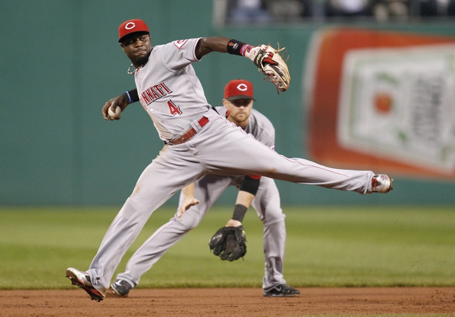 Sep 21, 2013; Pittsburgh, PA, USA; Cincinnati Reds second baseman Brandon Phillips (4) makes a throw on a ball up the middle in front of shortstop Zack Cozart (rear) against the Pittsburgh Pirates during the first inning at PNC Park. Mandatory Credit: Charles LeClaire-USA TODAY Sports