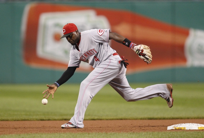 Sep 21, 2013; Pittsburgh, PA, USA; Cincinnati Reds second baseman Brandon Phillips (4) makes a bare-handed grab on a ball up the middle against the Pittsburgh Pirates during the first inning at PNC Park. Mandatory Credit: Charles LeClaire-USA TODAY Sports