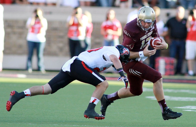 Sep 21, 2013; Lubbock, TX, USA; Texas State Bobcats quarterback Tyler Arndt (12) rushes against the Texas Tech Red Raiders in the first half at Jones AT&T Stadium. Mandatory Credit: Michael C. Johnson-USA TODAY Sports