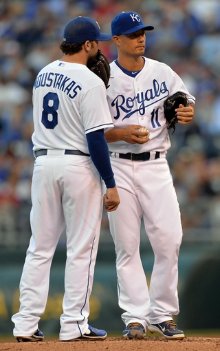 Sep 21, 2013; Kansas City, MO, USA; Kansas City Royals pitcher Jeremy Guthrie (11) talks with third basemen Mike Moustakas (8) against the Texas Rangers during the first inning at Kauffman Stadium. Mandatory Credit: Peter G. Aiken-USA TODAY Sports