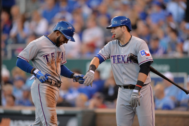Sep 21, 2013; Kansas City, MO, USA; Texas Rangers shortstop Elvis andrus (left) gets a hand after scoring from teammate Mitch Moreland (right) against the Kansas City Royals during the third inning at Kauffman Stadium. Mandatory Credit: Peter G. Aiken-USA TODAY Sports