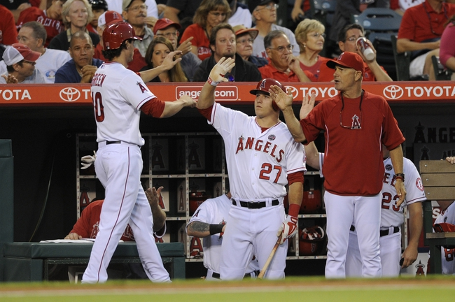 Sep 21, 2013; Anaheim, CA, USA; Los Angeles Angels second baseman Grant Green (10) celebrates with manager Mike Scioscia and center fielder Mike Trout (27) after running in a score off of an RBI single hit by third baseman Andrew Romine (not pictured) against the Seattle Mariners during the second inning at Angel Stadium of Anaheim. Mandatory Credit: Kelvin Kuo-USA TODAY Sports