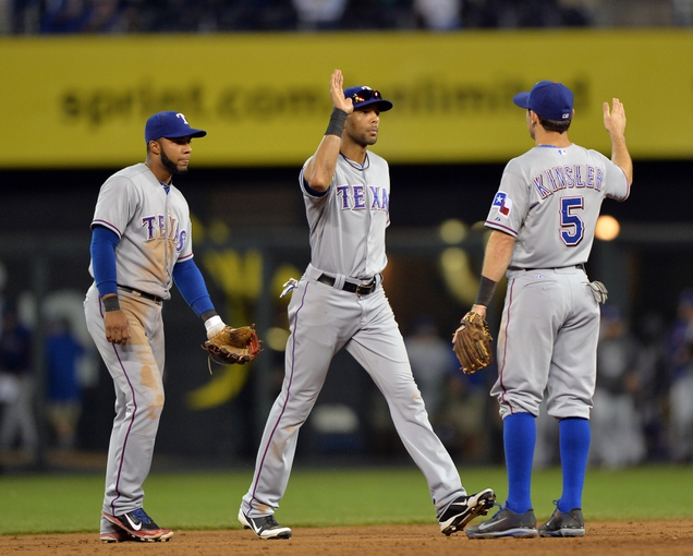 Sep 21, 2013; Kansas City, MO, USA; Texas Rangers players Elvis Andrus (left), Alex Rios (center) and Ian Kinsler (25) celebrate after beating the Kansas City Royals 3-1 at Kauffman Stadium. Mandatory Credit: Peter G. Aiken-USA TODAY Sports