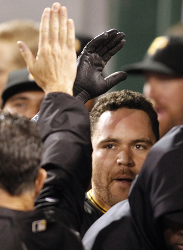 Sep 21, 2013; Pittsburgh, PA, USA; Pittsburgh Pirates catcher Russell Martin (right) is greeted in the dugout after hitting a two run home run against the Cincinnati Reds during the second inning at PNC Park. The Pittsburgh Pirates won 4-2. Mandatory Credit: Charles LeClaire-USA TODAY Sports
