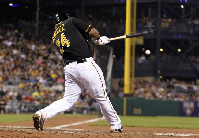 Sep 21, 2013; Pittsburgh, PA, USA; Pittsburgh Pirates third baseman Pedro Alvarez (24) hits an RBI single against the Cincinnati Reds during the sixth inning at PNC Park. The Pittsburgh Pirates won 4-2. Mandatory Credit: Charles LeClaire-USA TODAY Sports