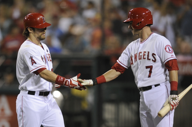 Sep 21, 2013; Anaheim, CA, USA; Los Angeles Angels left fielder Collin Cowgill (19) celebrates with Los Angeles Angels third baseman Andrew Romine (7) after hitting a solo run home run against the Seattle Mariners during the fourth inning at Angel Stadium of Anaheim. Mandatory Credit: Kelvin Kuo-USA TODAY Sports
