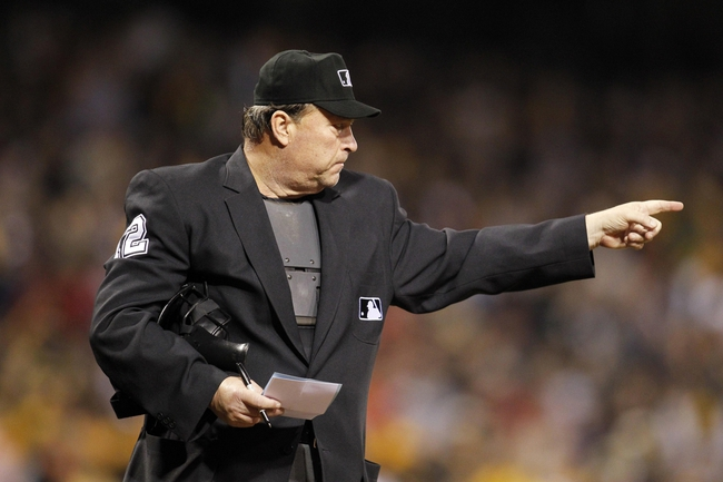 Sep 21, 2013; Pittsburgh, PA, USA; Home plate umpire Gerry Davis (12) gestures to signal a pitching change in the seventh inning of the game between the Cincinnati Reds and the Pittsburgh Pirates at PNC Park. The Pittsburgh Pirates won 4-2. Mandatory Credit: Charles LeClaire-USA TODAY Sports