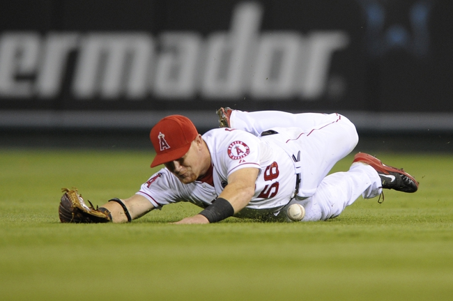 Sep 21, 2013; Anaheim, CA, USA; Los Angeles right fielder Kole Calhoun (56) misses a catch as he dives for a ball hit by Seattle Mariners catcher Henry Blanco (not pictured) during the sixth inning at Angel Stadium of Anaheim. Mandatory Credit: Kelvin Kuo-USA TODAY Sports