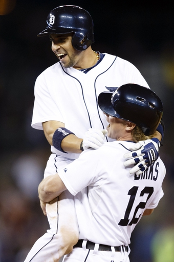 Sep 21, 2013; Detroit, MI, USA; Detroit Tigers left fielder Andy Dirks (12) lifts second baseman Omar Infante (4) off the ground after Infante hit a game winning RBI single in the twelfth inning against the Chicago White Sox at Comerica Park. Detroit won 7-6. Mandatory Credit: Rick Osentoski-USA TODAY Sports