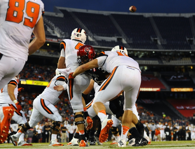 Sep 21, 2013; San Diego, CA, USA; Oregon State Beavers quarterback Sean Mannion (4) is hit as he releases the ball in the end zone during the second half against the San Diego State Aztecs at Qualcomm Stadium. Mandatory Credit: Christopher Hanewinckel-USA TODAY Sports