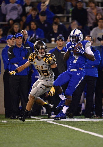 Sep 21, 2013; Colorado Springs, CO, USA; Air Force Falcons wide receiver Garrett Brown (7) pulls in a reception as Wyoming Cowboys linebacker Lucas Wacha (45) defends in the first quarter at Falcon Stadium. Mandatory Credit: Ron Chenoy-USA TODAY Sports