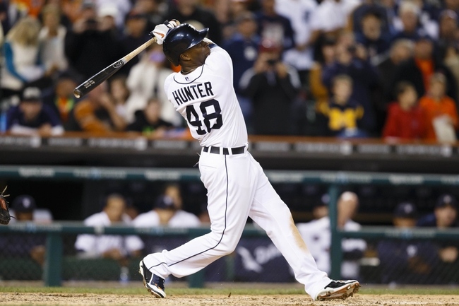 Sep 21, 2013; Detroit, MI, USA; Detroit Tigers right fielder Torii Hunter (48) hits a sacrifice fly to score second baseman Omar Infante (not pictured) to tie the game six to six in the ninth inning against the Chicago White Sox at Comerica Park. Mandatory Credit: Rick Osentoski-USA TODAY Sports