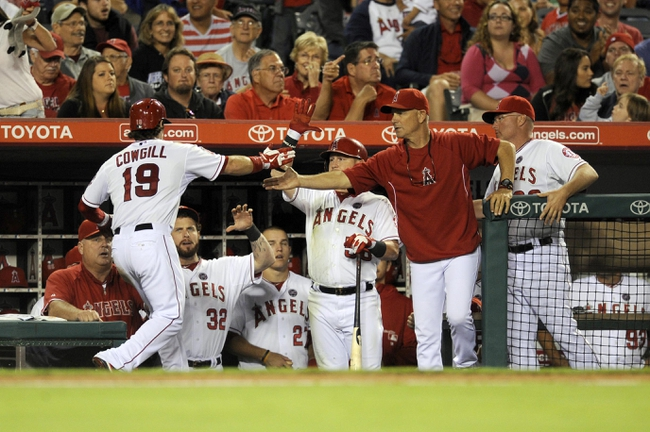 Sep 21, 2013; Anaheim, CA, USA; Los Angeles Angels left fielder Collin Cowgill (19) celebrates after scoring on a wild pitch by Seattle Mariners pitcher Joe Saunders (not pictured) during the seventh inning at Angel Stadium of Anaheim. Mandatory Credit: Kelvin Kuo-USA TODAY Sports