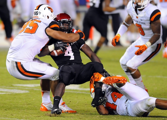 Sep 21, 2013; San Diego, CA, USA; San Diego State Aztecs running back Adam Muema (4) is tackled by Oregon State Beavers defensive end Scott Crichton (95) and linebacker Jabral Johnson (44) for a loss during the second half at Qualcomm Stadium. Mandatory Credit: Christopher Hanewinckel-USA TODAY Sports