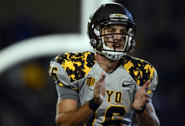 Sep 21, 2013; Colorado Springs, CO, USA; Wyoming Cowboys quarterback Brett Smith (16) reacts to his six yard rushing touchdown against the Air Force Falcons in the second quarter at Falcon Stadium. Mandatory Credit: Ron Chenoy-USA TODAY Sports