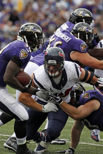 Sep 22, 2013; Baltimore, MD, USA; Houston Texans defensive end J.J. Watt (99) attempts to tackle Baltimore Ravens running back Bernard Pierce (30) at M&T Bank Stadium. Mandatory Credit: Mitch Stringer-USA TODAY Sports