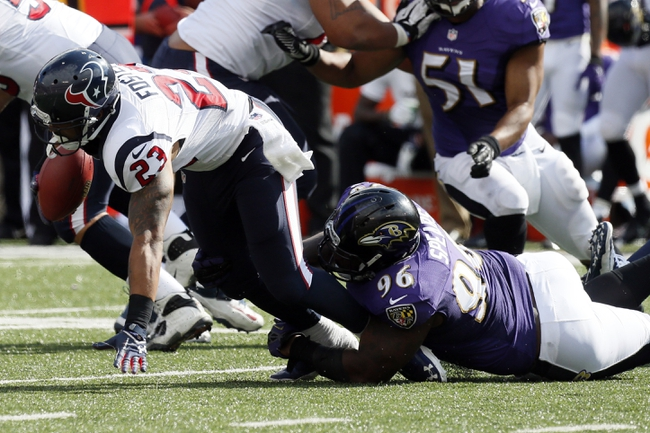 Sep 22, 2013; Baltimore, MD, USA; Houston Texans running back Arian Foster (23) is tackled for a loss by Baltimore Ravens defensive end Marcus Spears (96) at M&T Bank Stadium. Mandatory Credit: Mitch Stringer-USA TODAY Sports