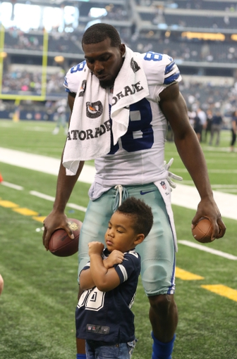 Sep 22, 2013; Arlington, TX, USA; Dallas Cowboys receiver Dez Bryant (88) plays with his son Dez Bryant Jr after the game against the St. Louis Rams at AT&T Stadium. The Dallas Cowboys beat St. Louis Rams 31-7. Mandatory Credit: Matthew Emmons-USA TODAY Sports