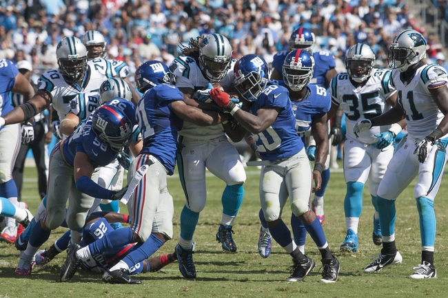 Sep 22, 2013; Charlotte, NC, USA;  Carolina Panthers running back DeAngelo Williams (34) gets stopped by New York Giants free safety Ryan Mundy (21) and cornerback Prince Amukamara (20) during the third quarter at Bank of America Stadium. The Panthers defeated the Giants 38-0.  Mandatory Credit: Jeremy Brevard-USA TODAY Sports