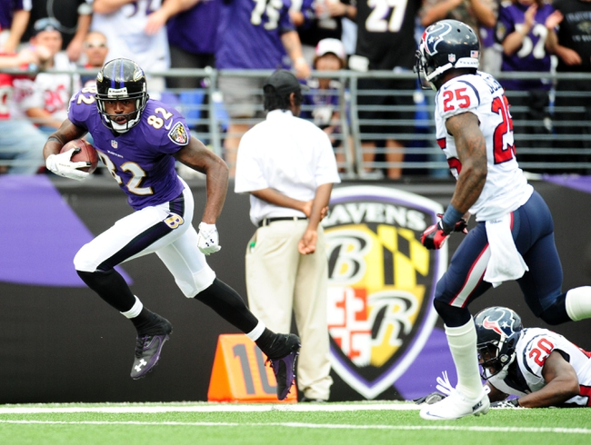 Sep 22, 2013; Baltimore, MD, USA; Baltimore Ravens wide receiver Torrey Smith (82) breaks the tackle of Houston Texans safety Ed Reed (20) and runs away from cornerback Kareem Jackson (25) at M&T Bank Stadium. Mandatory Credit: Evan Habeeb-USA TODAY Sports