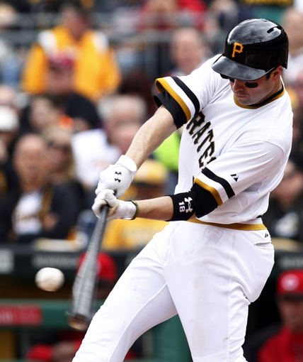 Sep 22, 2013; Pittsburgh, PA, USA; Pittsburgh Pirates second baseman Neil Walker (18) hits a solo home run against the Cincinnati Reds during the third inning at PNC Park. The Reds won 11-3. Mandatory Credit: Charles LeClaire-USA TODAY Sports
