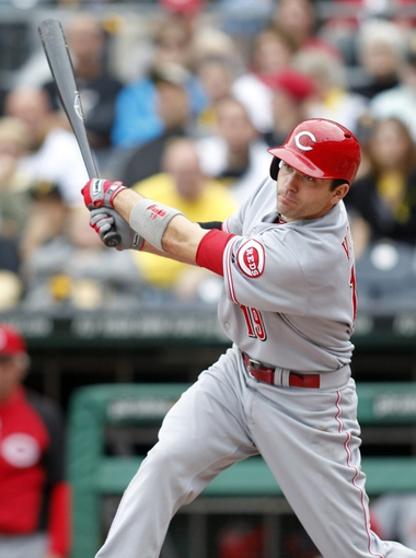 Sep 22, 2013; Pittsburgh, PA, USA; Cincinnati Reds first baseman Joey Votto (19) hits an RBI single against the Pittsburgh Pirates during the eighth inning at PNC Park. The Reds won 11-3. Mandatory Credit: Charles LeClaire-USA TODAY Sports