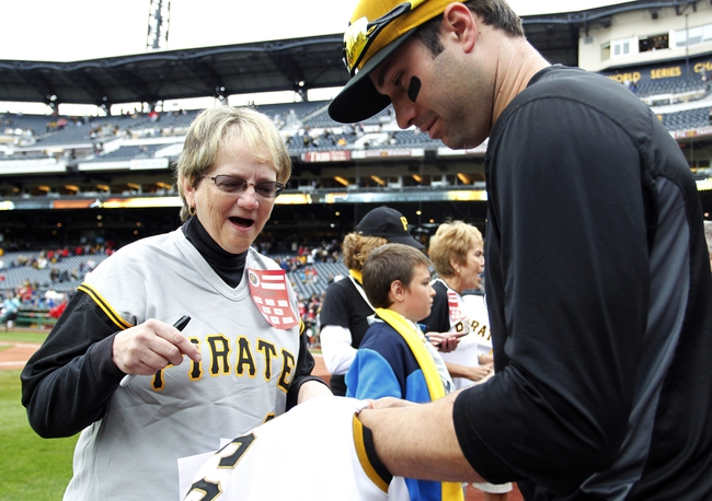 Sep 22, 2013; Pittsburgh, PA, USA; Pittsburgh Pirates fan receives a game used jersey from second baseman Neil Walker (18) as part of a shirt off their backs promotion following the game against the Cincinnati Reds at PNC Park. The Reds won 11-3. Mandatory Credit: Charles LeClaire-USA TODAY Sports