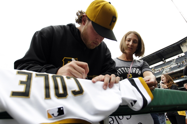 Sep 22, 2013; Pittsburgh, PA, USA; Pittsburgh Pirates starting pitcher Gerrit Cole (45) signs his game used shirt for a fan as part of a shirt off their backs promotion following the game against the Cincinnati Reds at PNC Park. The Reds won 11-3. Mandatory Credit: Charles LeClaire-USA TODAY Sports