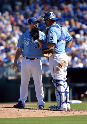 Sep 22, 2013; Kansas City, MO, USA; Kansas City Royals pitcher Greg Holland (56) talks with catcher Salvador Perez (13) against the Texas Rangers during the ninth inning at Kauffman Stadium. The Royals beat the Rangers 4-0. Mandatory Credit: Peter G. Aiken-USA TODAY Sports