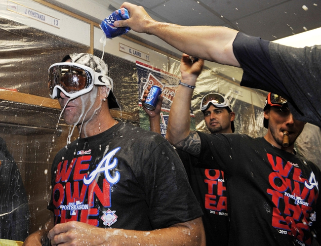 Sep 22, 2013; Chicago, IL, USA; Atlanta Braves pitcher Tim Hudson (left) celebrates in the locker room after the game against the Chicago Cubs at Wrigley Field. The Braves won 5-2 to clinch the National League eastern division championship. Mandatory Credit: David Banks/Pool Photo via USA TODAY Sports