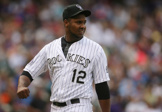 Sep 22, 2013; Denver, CO, USA; Colorado Rockies starting pitcher Juan Nicasio (12) walks back to the dugout after being relieved during the third inning against the Arizona Diamondbacks at Coors Field. Mandatory Credit: Chris Humphreys-USA TODAY Sports